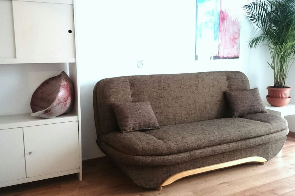 Livingroom with sofa bed and ceramic art