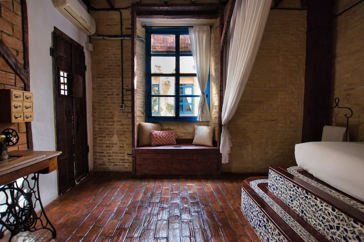 Sit on top of the hand made chest and look out the old style window to the downstairs courtyard.