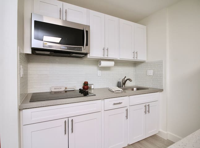 The kitchen is stocked with pots and pans, utensils, silverware, rice cooker, coffee pot.  Microwave has the convection oven feature