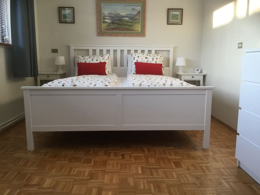 Wood-framed King-sized bed (180cm x 200cm) with deep, hand-stitched individual mattresses.