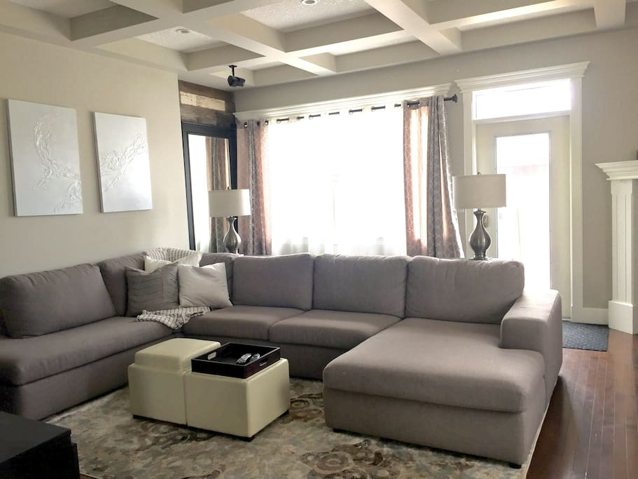 "Main floor living room. Lots of room for the entire family on this sectional. 65"" tv with Netflix preloaded for you enjoyment."