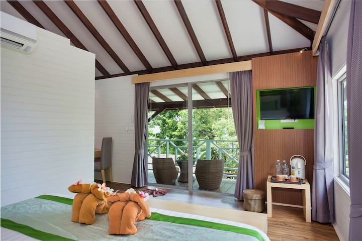 Bedroom with airconditioning, television a private balcony in a lush jungle setting.