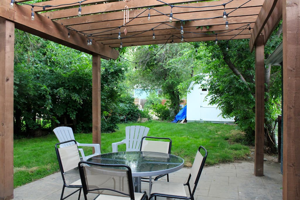 Back Patio dining under pergola and market lights with gas grill