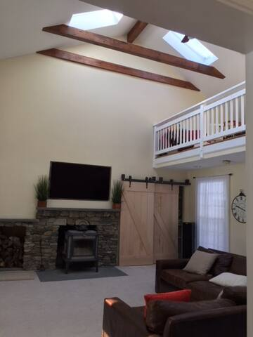 Sky lights and vaulted ceiling open to balcony, with fan.