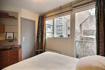 Bedroom: The 12 square meters bedroom is contiguous to the bathroom and has a large bay window facing courtyard . It is equipped with : double bed (1.40m), built-in wall closet, desk, hard wood floor.