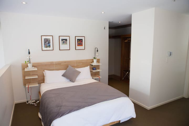 Loft master bedroom, with ensuite, walk-in wardrobe, lamps, phone chargers & Google assistant clock