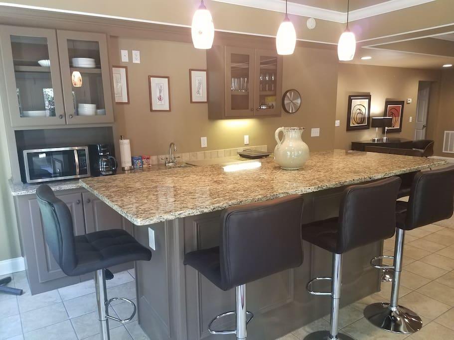 """Bar kitchen"" - Five bar stools around a stunning, one-piece granite countertop."