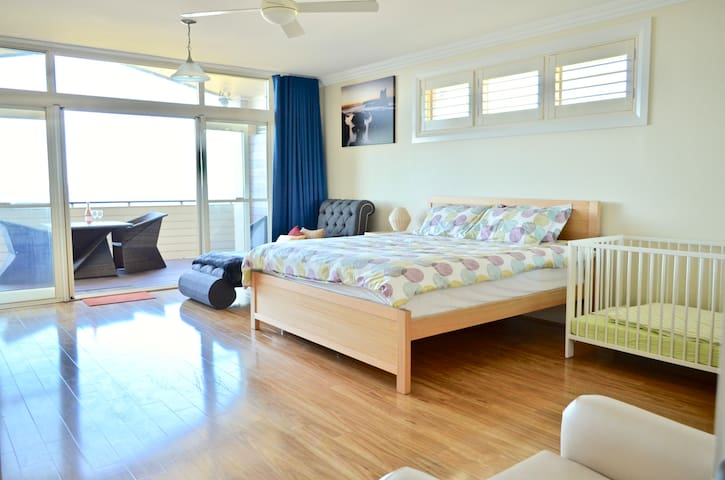 Upstairs master suite with king bed, ensuite, direct access to a private balcony space overlooking the ocean, and a cot for the little ones.