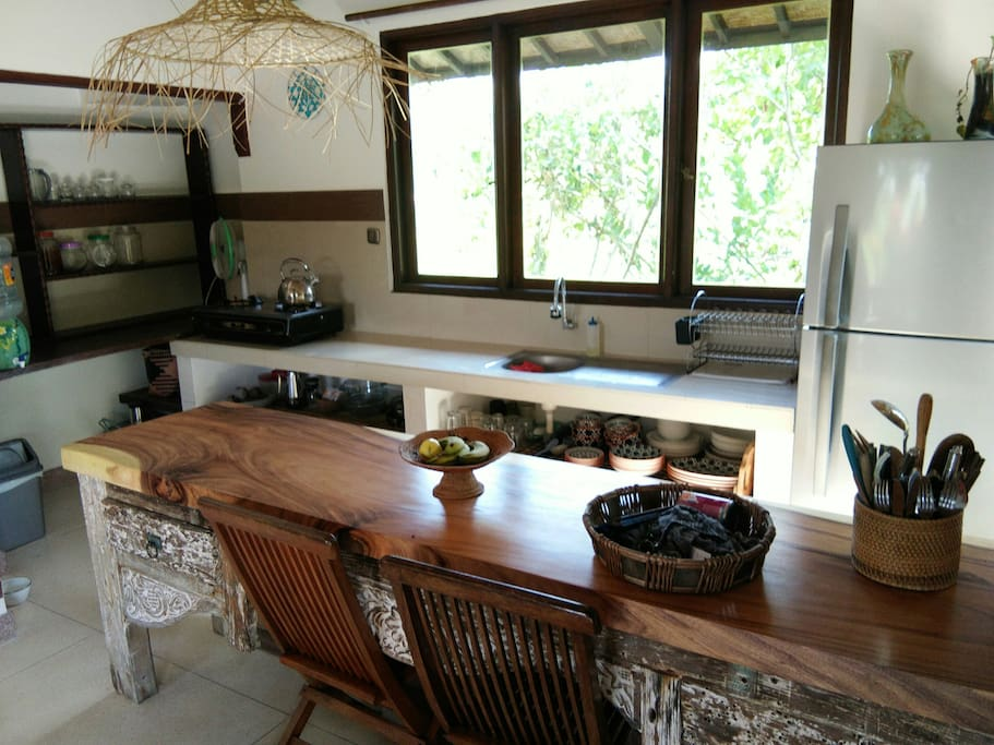 A fully equipped kitchen with a beautiful teak wooden counter top, window aspect faces the rice fields and garden