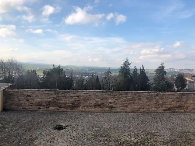 """Scorcio di panorama con le montagne all'orizzonte visibili da quello che gli abitanti del posto chiamano """"il Belvedere""""."""