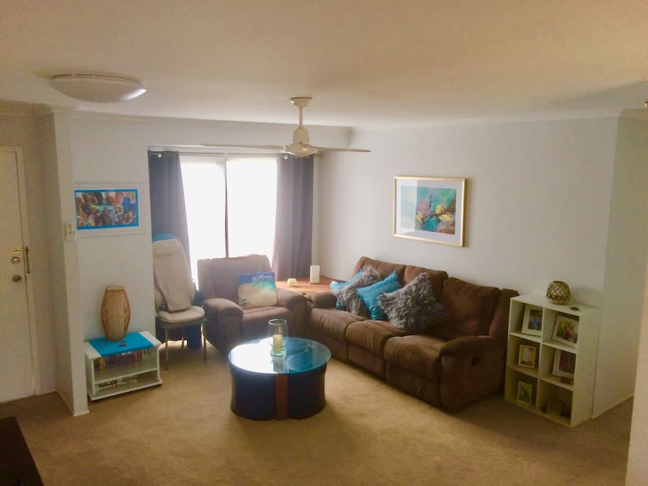 Lounge room with 3 recliners massage chair, entertainment unit and aircon.