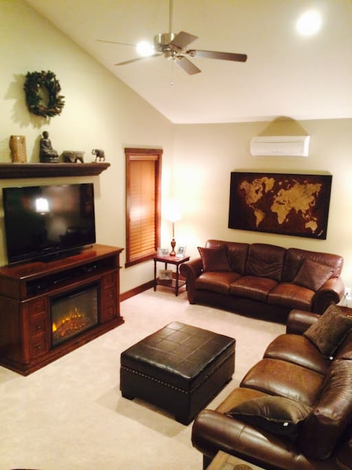 Carpeted living room with 2 leather couches and a leather recliner/rocker, large screen TV, cable, Netflix, & X-box.