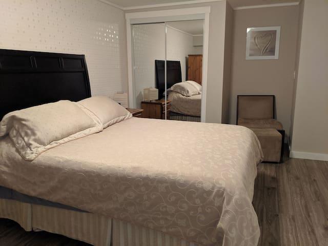 Spacious queen bedroom, closet with hangers.