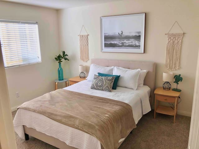 Master Bedroom with plush queen bed sleeps two. View of green hillside/pool.