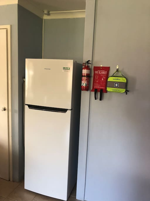 Fridge, fire extinguisher, fire blanket and first aid kit.