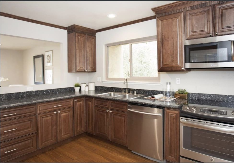Large kitchen with microwave, electric stove, oven, dishwasher and refrigerator.