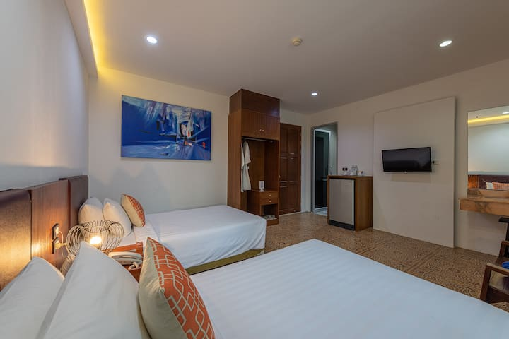Cosy studio room with twin beds, TV, fridge, private shower room & toilet.