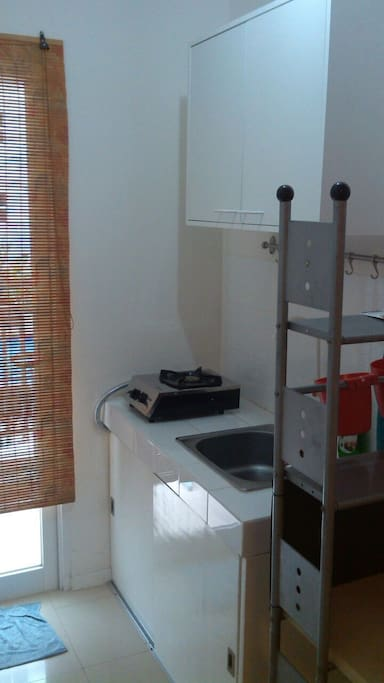 Pantry next to balcony door with wash basin, stove and kitchen ware