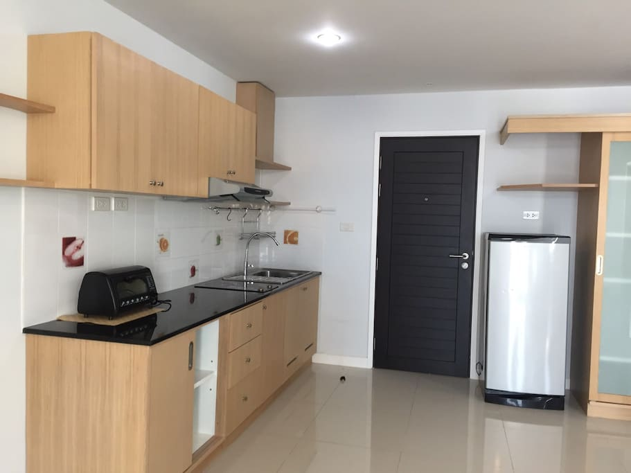 Kitchen is fully equipped with stove, fridge, and small over.
