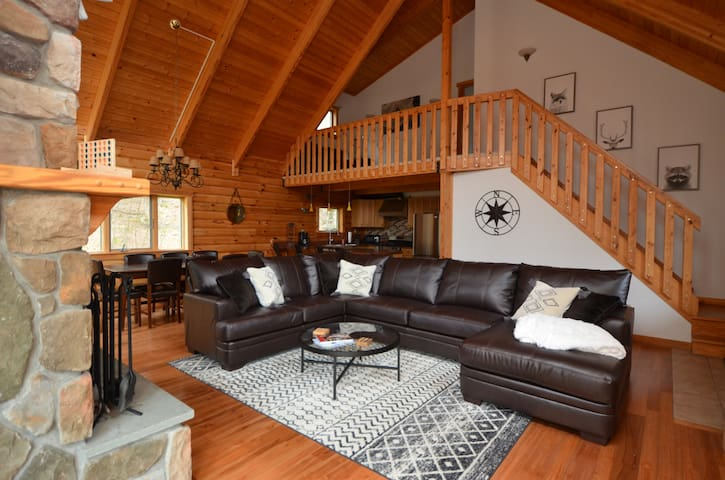 The open floor plan and cathedral ceilings create a cozy space with plenty of comfortable seating