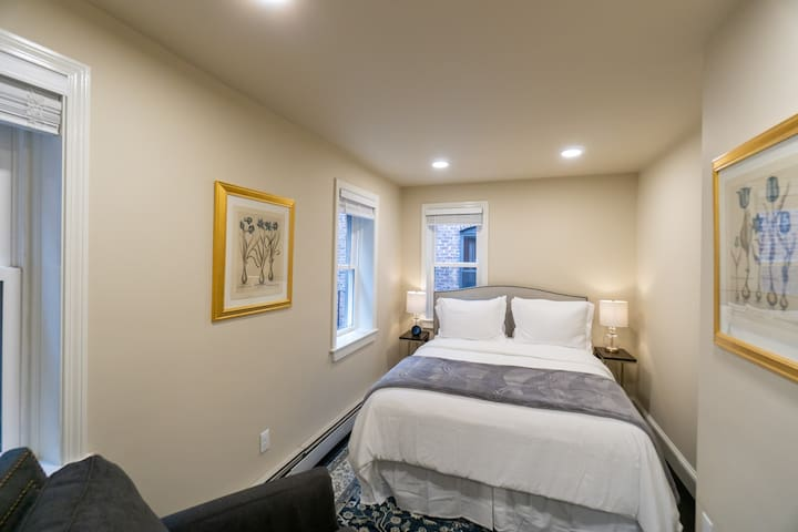 Bedroom features a queen size bed, two night stands, a sitting chair, and a closet