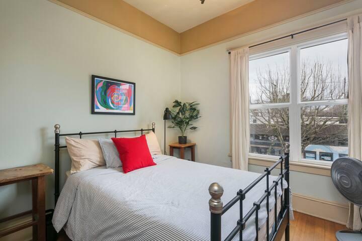 Cozy, light, master bedroom with queen bed.