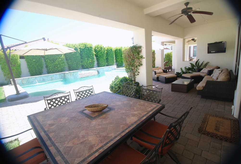 """East Patio overlooking the pool. Outdoor Living Room. 32"""" RokuTV. Dining for 8."""