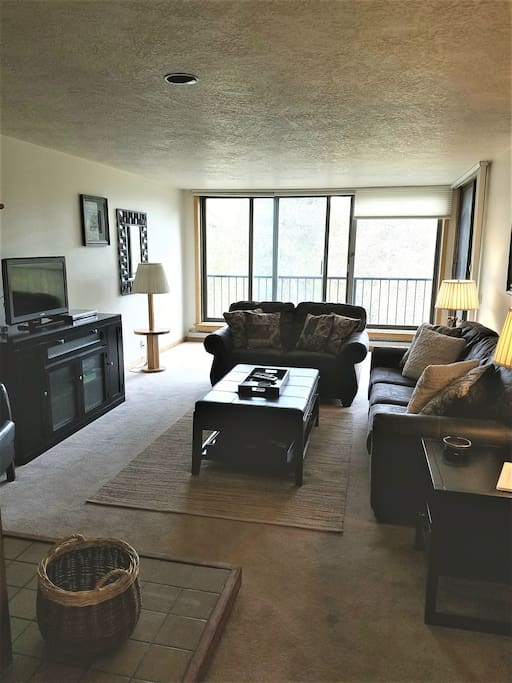Spacious family room with cozy fireplace and floor to ceiling views of the mountains