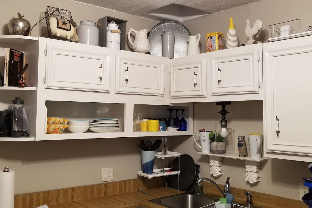 toaster, coffee maker, open shelving in kitchen with glasses, dishes etc