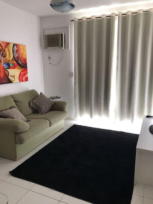 sala ampla com ar condicionado, sofá cama casal e tv.
