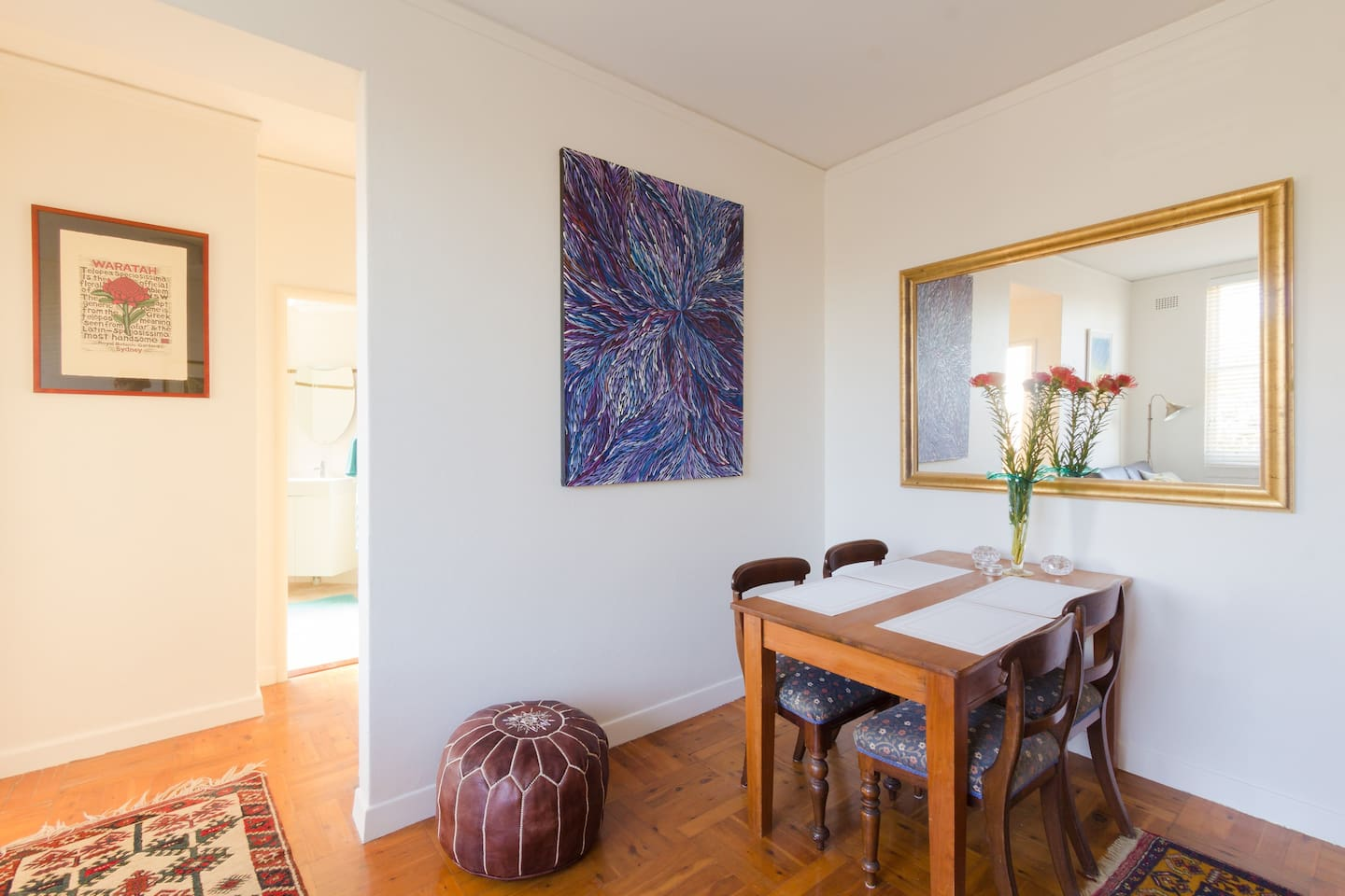 Sunny lounge and dining room with parquetry floors, rugs