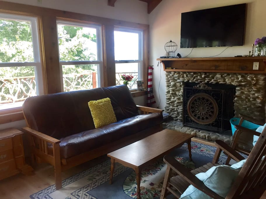 Living room, with brand new, extra comfortable leather futon, rocking chairs, TV, and wood burning fireplace. Amazing views from windows