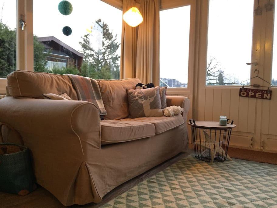 Relax op de stoffen bank met kussens. Relax on the sofa with cushions.