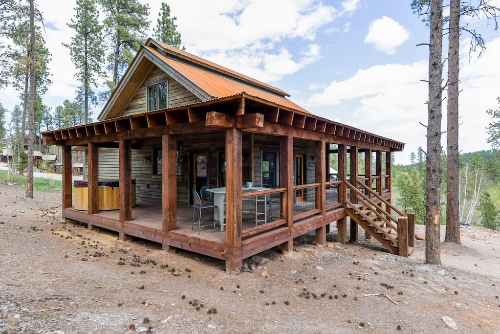 Rear view of the cabin in the summer with hot tub.