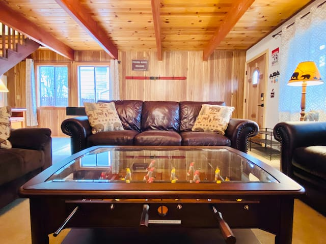Spacious living room with fun family time playing foosball.