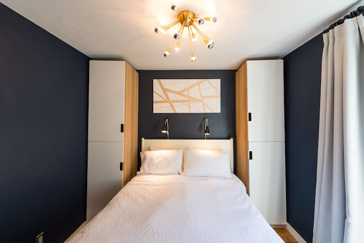 Petite bedroom with ample storage, queen sized Serta memory foam mattress, down alternative comforter, Egyptian- cotton high thread-count sheets, and custom paintings and light fixtures.
