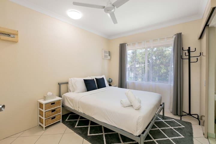 The bedroom offers a plush queen bed and plenty of storage space.