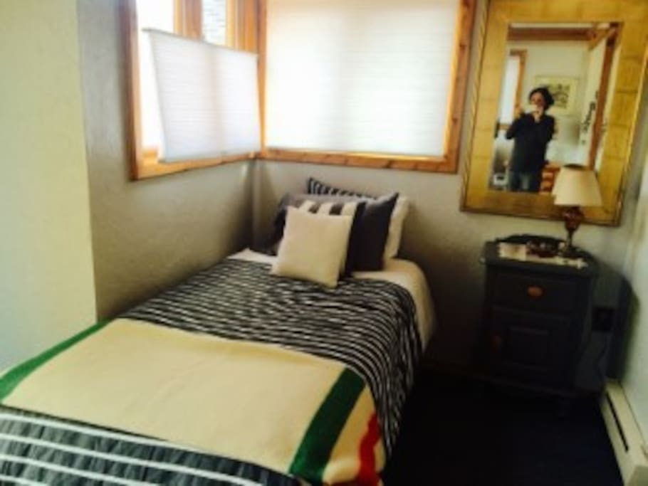 East twin bed with luxury linens and lots of windows for taking in the scenery