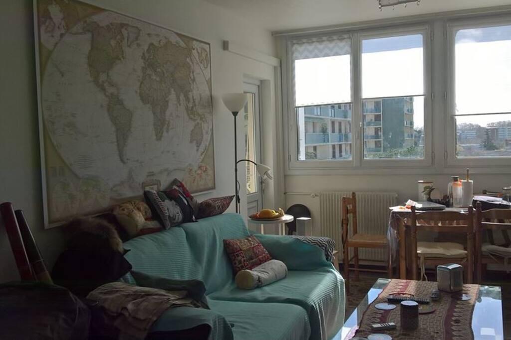"""Coin living room donnant sur un petit balcon, lui même accessible par la chambre """"bibliothèque"""". Vue sur le métro depuis les fenêtres du living room."""