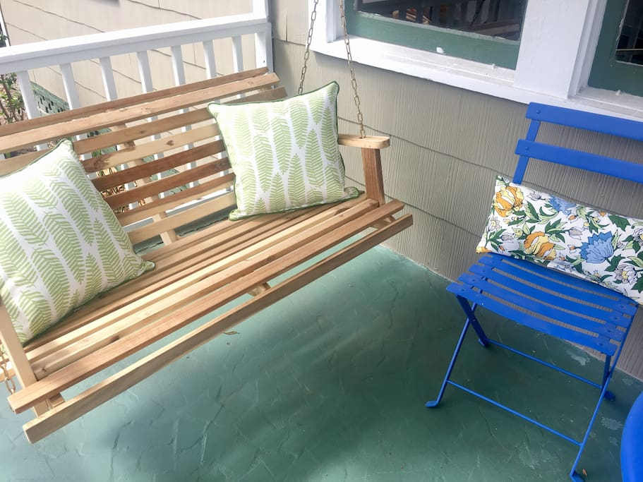 Cheery front porch with swing and cafe table. This is my favorite place to hang out and feel the breeze!