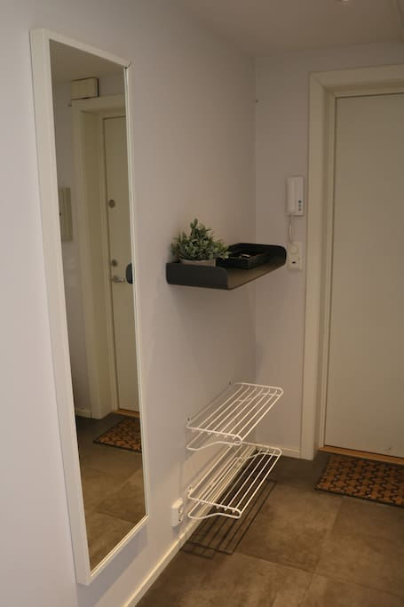 Shoe racks and full size mirror in the hallway.