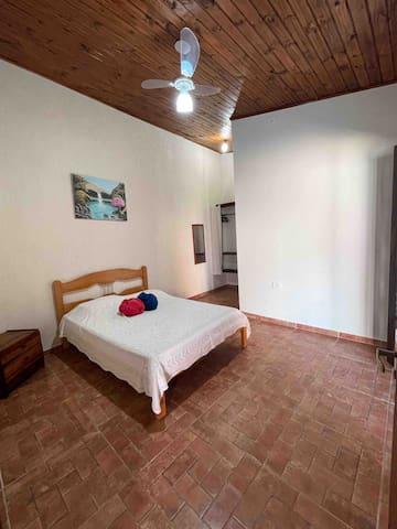 Quarto I suíte, com uma cama de casal e ventilador de teto .