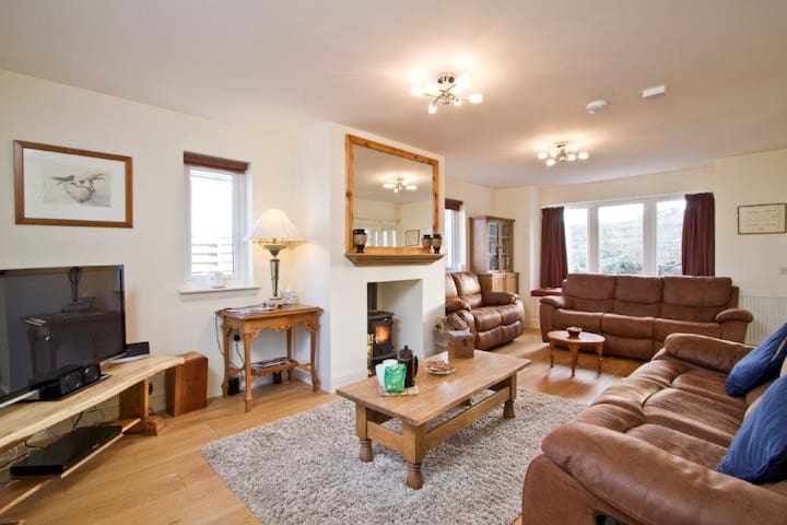 Spacious living room with flat screen television, unlimited WI-FI and wood burning stove