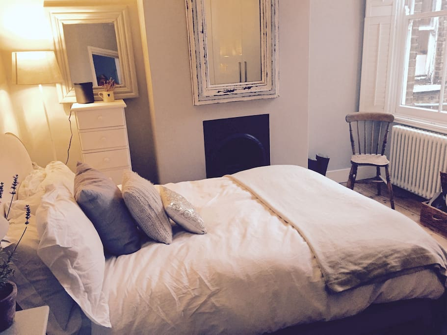 Bedroom 1 - white wooden shutters & a Victorian fireplace.