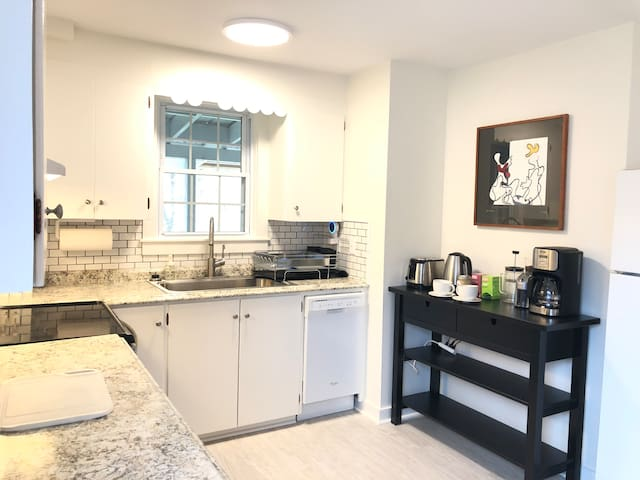 View of kitchen. Includes dishwasher, toaster and fixings for a coffee or tea drinker, such as coffee beans and grinder, french press and drip coffee maker, and an electronic kettle.
