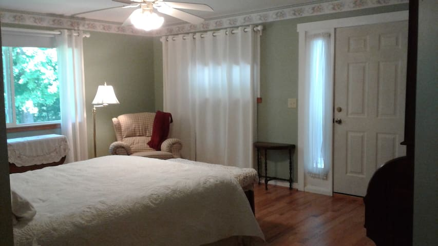 Rose Room with comfy recliner and hardwood floor. Door leads to private covered porch.