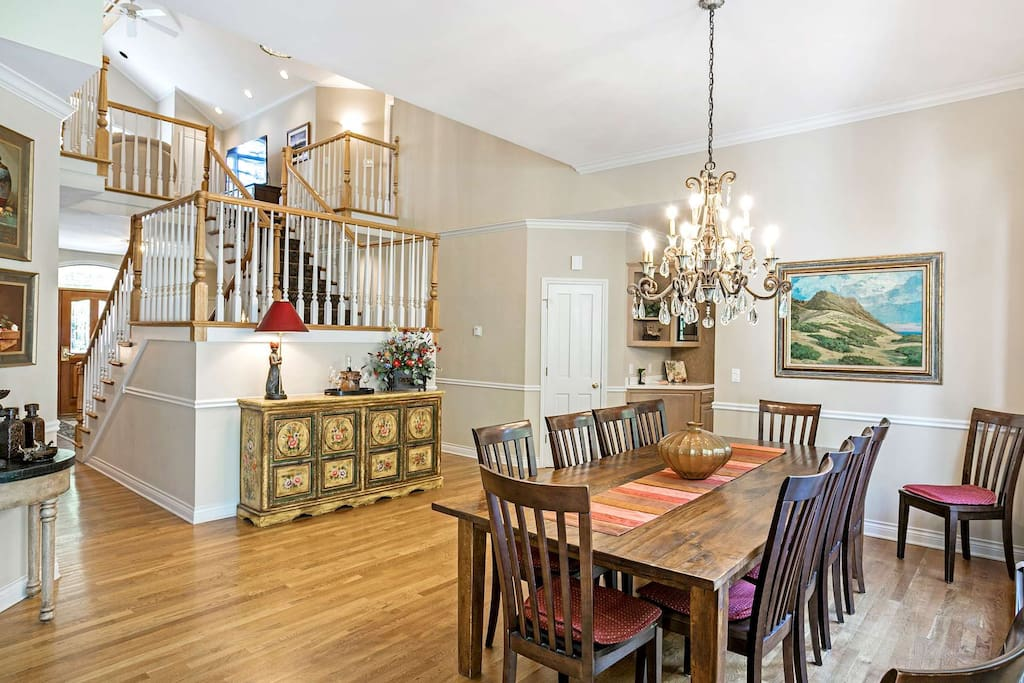 Grand foyer with view of stairs leading to bedrooms 2 & 3, upstairs den and large dining table to gather with friends and family.