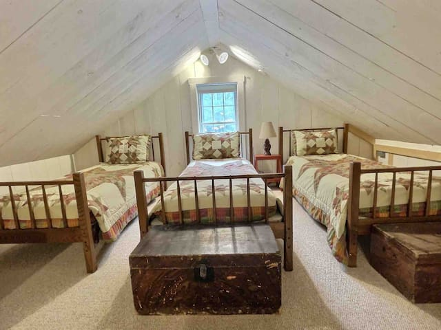 Three charming twin beds in the sleeping loft. Stories and laughs will be shared until it is time for lights out.