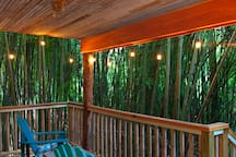 This is our large expansive treehouse porch with a beautiful view of the bamboo forest.  Unwind as you listen to our specific birds and barred owls, sip a beverage and bond with your special someone.  Photo by Lindsay Appel