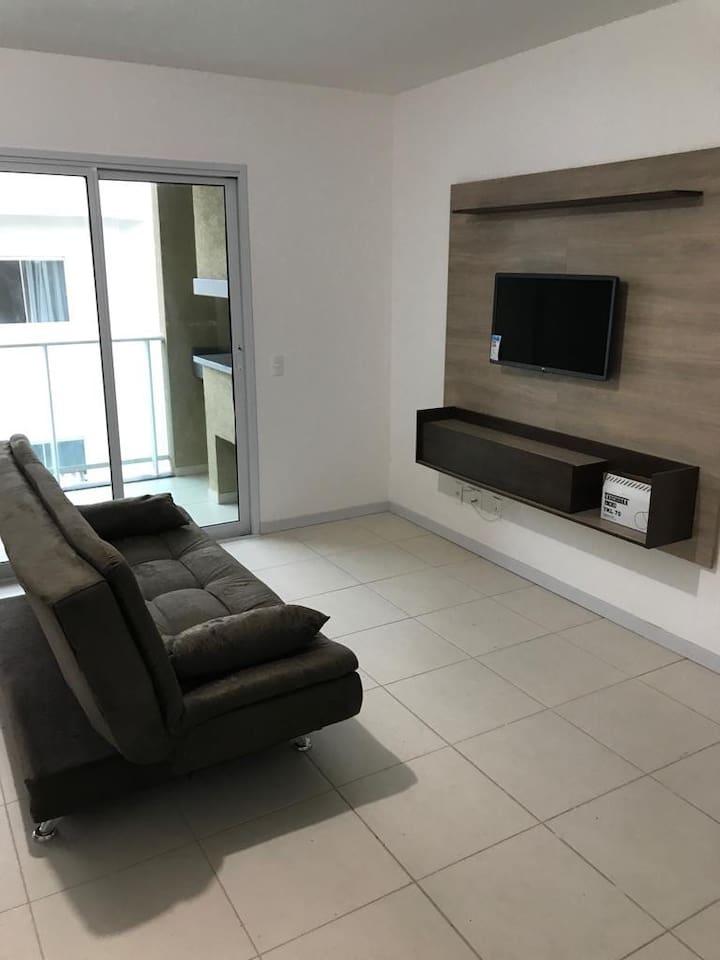 Sala com sofá confortável e tv. Varanda com churrasqueira